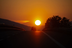 Motorway sunset, with holidaymaker cars returning from vacation, holiday. Homeward bound. Genuine image. Large sun.